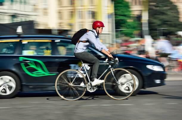 Велосипедист едет на улице рядом с автомобилем ДВС