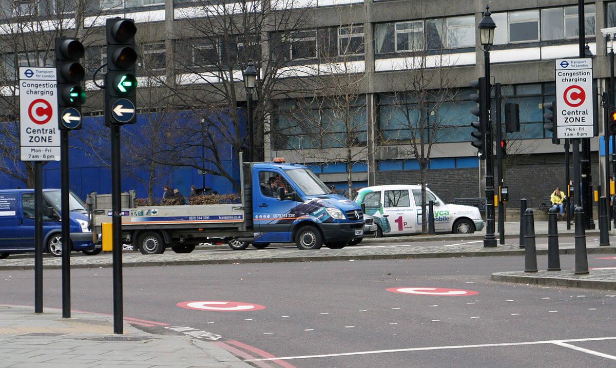 Платный въезд в Лондоне:разметка и знак с красным кружком с белой буквой С предупреждает водителей о плате за въезд