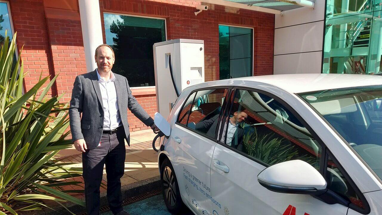 Крейг Прендергаст, региональный менеджер поперсоналу, заряжает  Volkswagen e-Golf вштаб-квартире ABB вВеликобритании